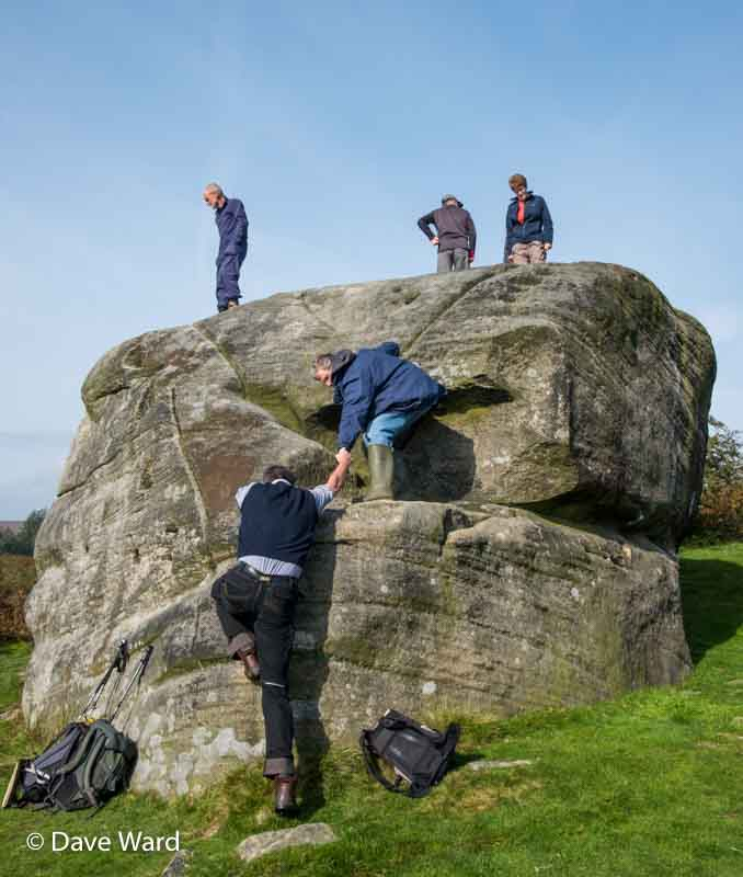 Climbing on the Buck Stone to see the inscriptions